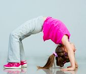 stock photo of leg-split  - Little girl doing gymnastics exercise - JPG