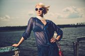 Stylish beautiful blond woman wearing white scarf and sunglasses  standing near rails of old pier