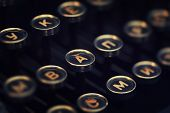 Vintage typewriter keyboard macro closeup. Shallow DOF, focus on letter