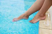 foto of wet feet  - a female legs in the water pool - JPG