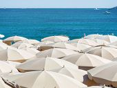 many umbrellas on the beach, symbolic photo for holidays, mass tourism, sunburn