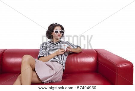 Young woman on a couch posing with a cup of coffee