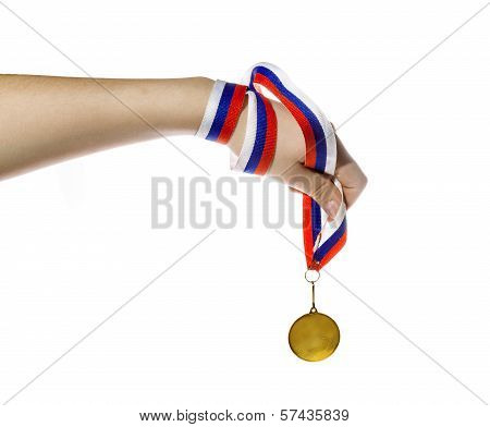 Gold Medal On A Ribbon In A Child's Hand On A White Background