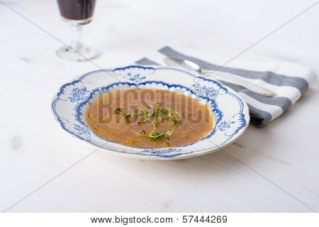 Classic French Onion Soup On A White Wood Table With Some Red Wine And A Silver Spoon On The Side