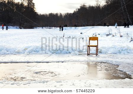 Icebound Chair Near Opening Water In Frozen Lake