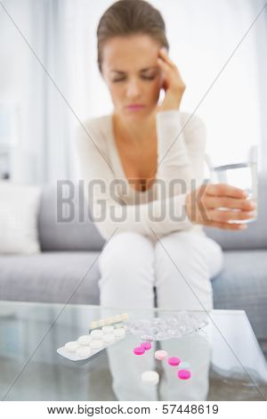 Closeup On Pills And Feeling Bad Young Woman In Background