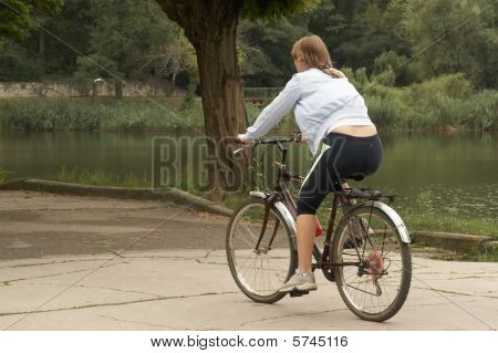 Young Woman Riding With Bike