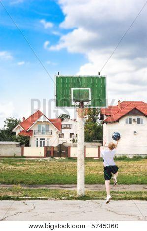 Young Boy Playing Basketball Alone