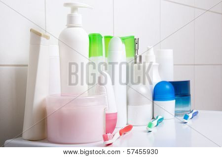 Collection Of White Cosmetic Bottles Over Tiled Wall