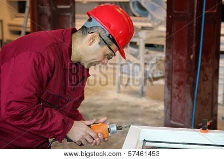 Worker Using Power Tool In Workshop