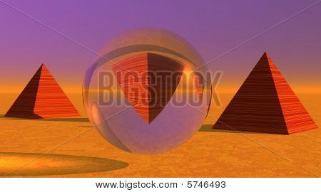 eine Pyramide kopfüber in eine Kugel und zwei weitere in der Wüste