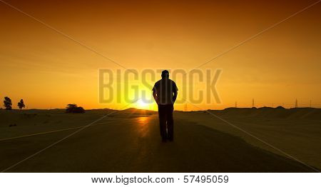 Man walking on the road with relax mood. Desert road in Dubai, UAE