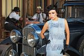 stock photo of gangster necklace  - Beautiful 1920s female in blue near retro automobile