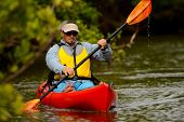 stock photo of canoe boat man  - young man in kayak in a tropical location