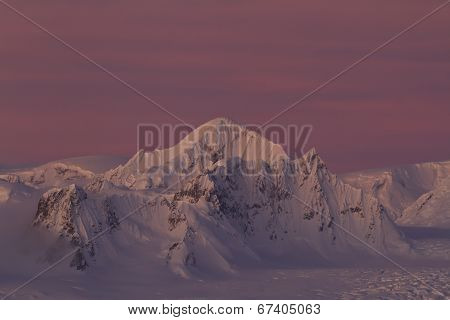 Shackleton Peak In A Chain Of Mountains In The Antarctic Peninsula Against A Red Sky