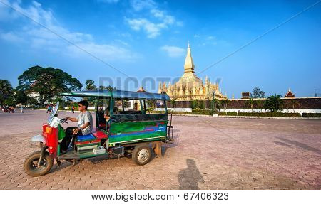 VIENTIANE, LAOS - 11 DEC,2013: Unidentified tuk tuk taxi driver near golden pagoda wat Phra That Luang in Vientiane. Famous tourist destination
