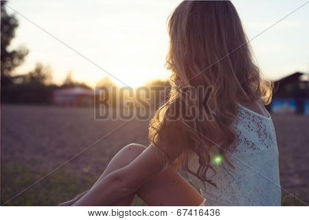 Sunny portrait of a beautiful young romantic woman or girl in white dress on beach watching the suns