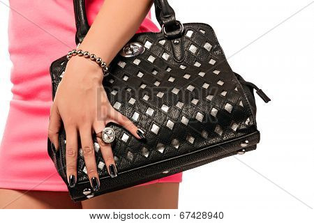 Closeup of woman in pink mini dress. Wearing a fashion leather bag. Isolated on the white studio background.