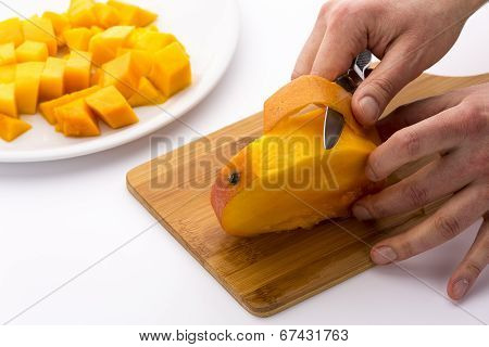 Peeling the Mango slice containing the fruit pit