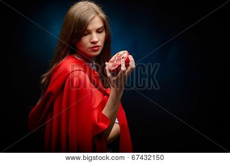 beautiful woman with red cloak holding pomegranate in her hand