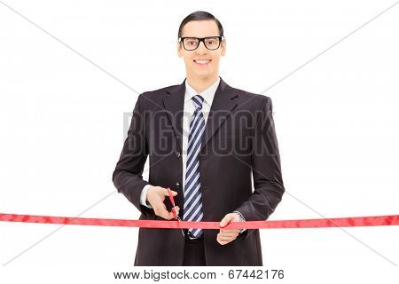 Businessman cutting a red tape isolated on white background
