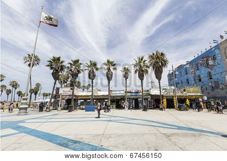 LOS ANGELES, CALIFORNIA - JUNE 20, 2014:  Shops and palm trees along the funky Windward Plaza at Venice Beach in Los Angeles, California.