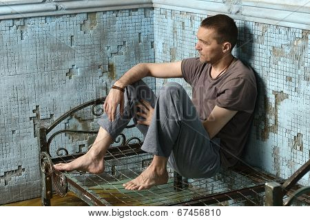 Man on the metal rusty bed