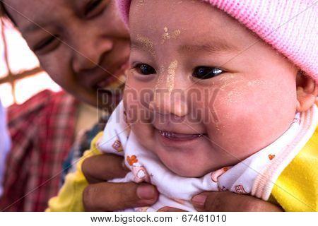 KYAIKTO MYANMAR - DEC 14 2012: An Burmese woman with her baby in December 14 2012 in Kyaikto Myanmar
