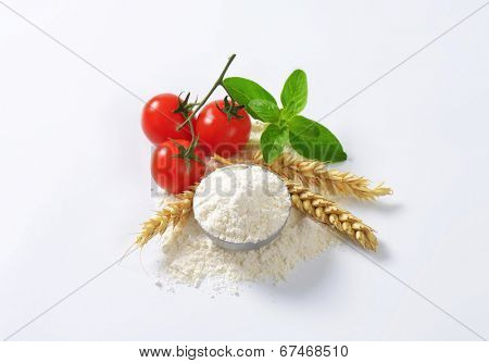 bowl of flour with wheat ear and fresh tomatoes