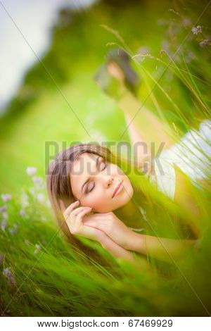 Beautiful Young Woman Sleeping Among Grass And Flowers