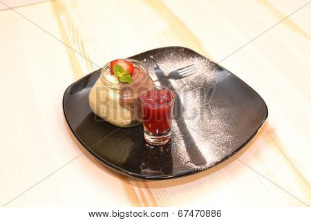 Pudding in glass with red strawberry sauce