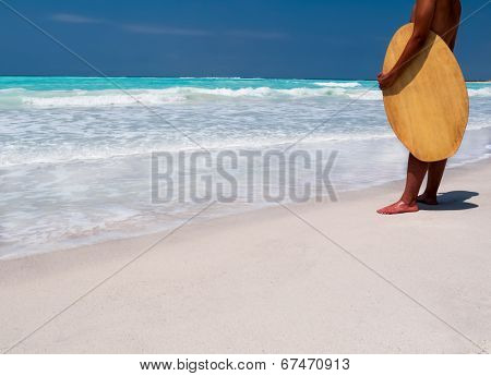 Rear view of male surfer with surfboard standing on a tropical beach. Sunny clear summer day.