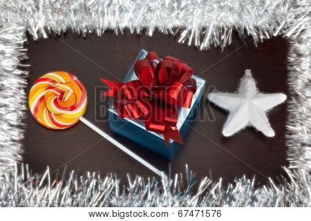 Blue Gift Box, Candycane And White Christmas Star On Black Wood