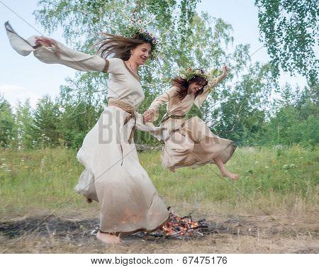 Attractive girls jump through fire