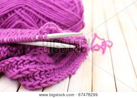 Knitting with spokes on wooden background
