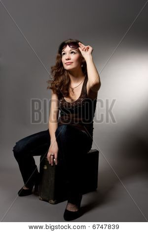sitting young caucasian dark hair woman with suitcase isolated over gray