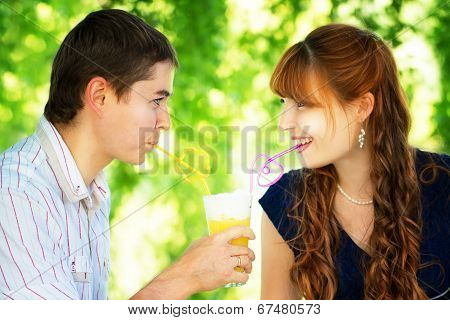 Beautiful Young Couple Drinking Juice From One Glass With Colored Tubes. Picnic In Countryside. Happ
