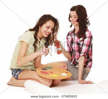 Two beautiful girls with a brush and  palette, sittting