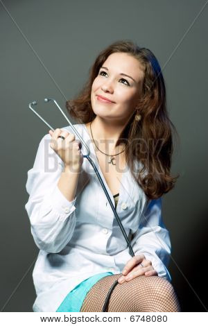 thinking young female caucasian doctor with endoscope smiling isolated over gray