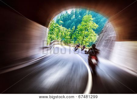 Group of bikers touring along European mountains, riding in tunnel, extreme lifestyle, slow motion, traveling and tourism concept