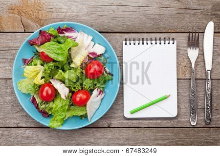 Fresh healthy salad with tomatoes and utensils on wooden table. Healthy food