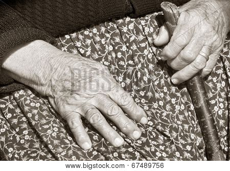 Close up of elderly womans hand resting on her walking stick