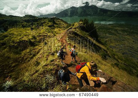Group of hikers crossing rocky obstacle in the mountains
