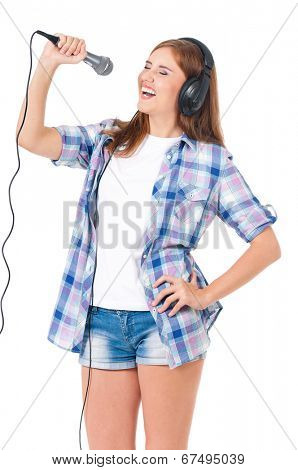 Beautiful teen girl posing on a white background with a microphone and headphones