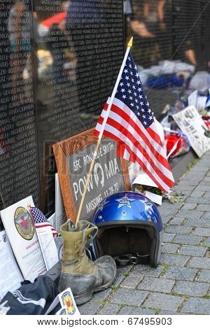 WASHINGTON, D.C. - MAY 26, 2014: People visit and lay flowers and other souvenirs  at the Vietnam Veterans Memorial on May 26, 2014, in Washington, D.C.