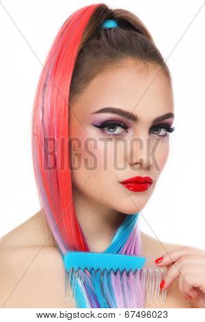 Portrait of young beautiful tanned girl with colorful ponytail and comb in her hand over white background