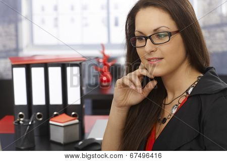 Portrait of young businesswoman thinking at workplace.
