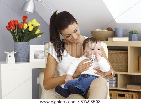 Young mother sitting in armchair at home, holding little boy in arms, smiling. Teat in mouth.