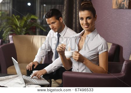 Young woman having coffee at hotel lobby, working late with colleague on business trip.