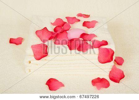 Towels and soap under petals of roses